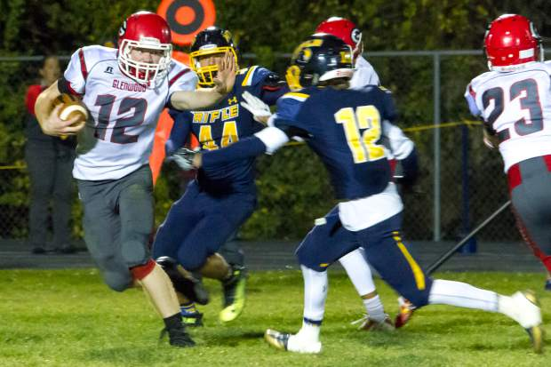 Demons QB Jake Townsley(12) works to get past the Rifle Bears defense during Friday night's game at Rifle High School.