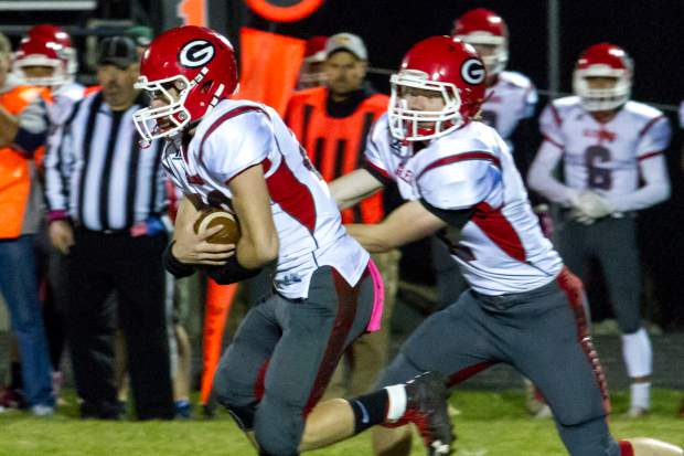 Demons QB Jake Townsley hands the ball off to Easton Gaddis during Friday night's match-up at Rifle High School.