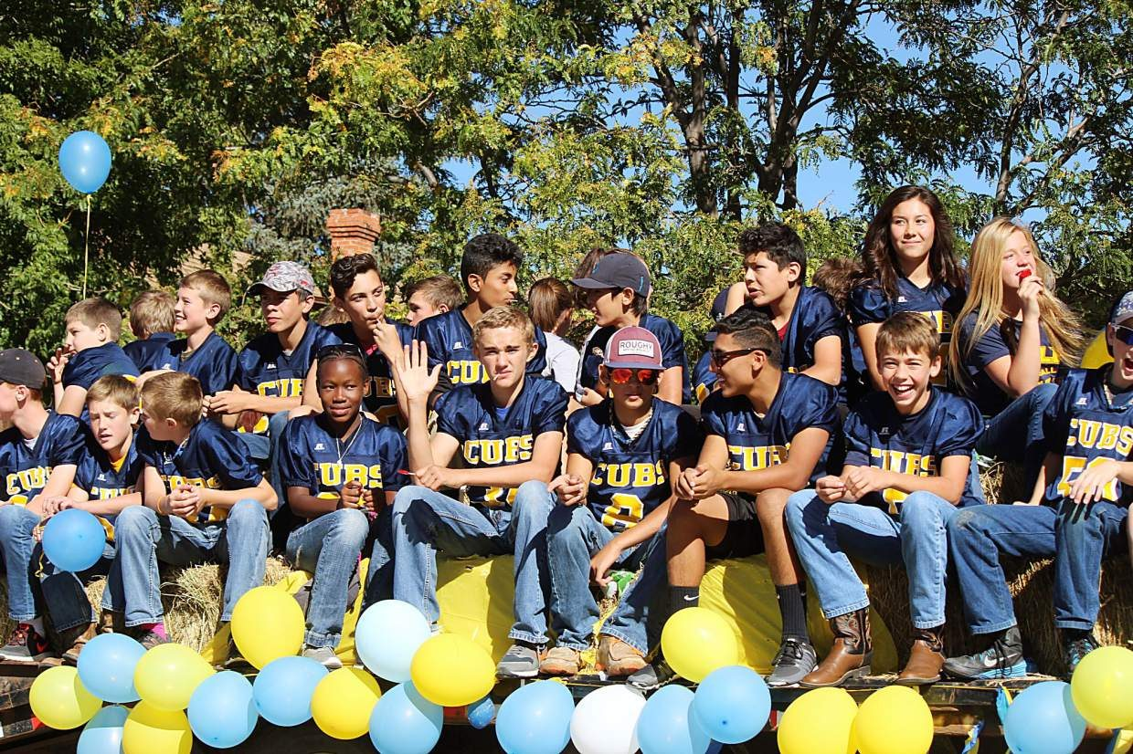 Players on the Rifle Middle School football team waive during the homecoming parade.