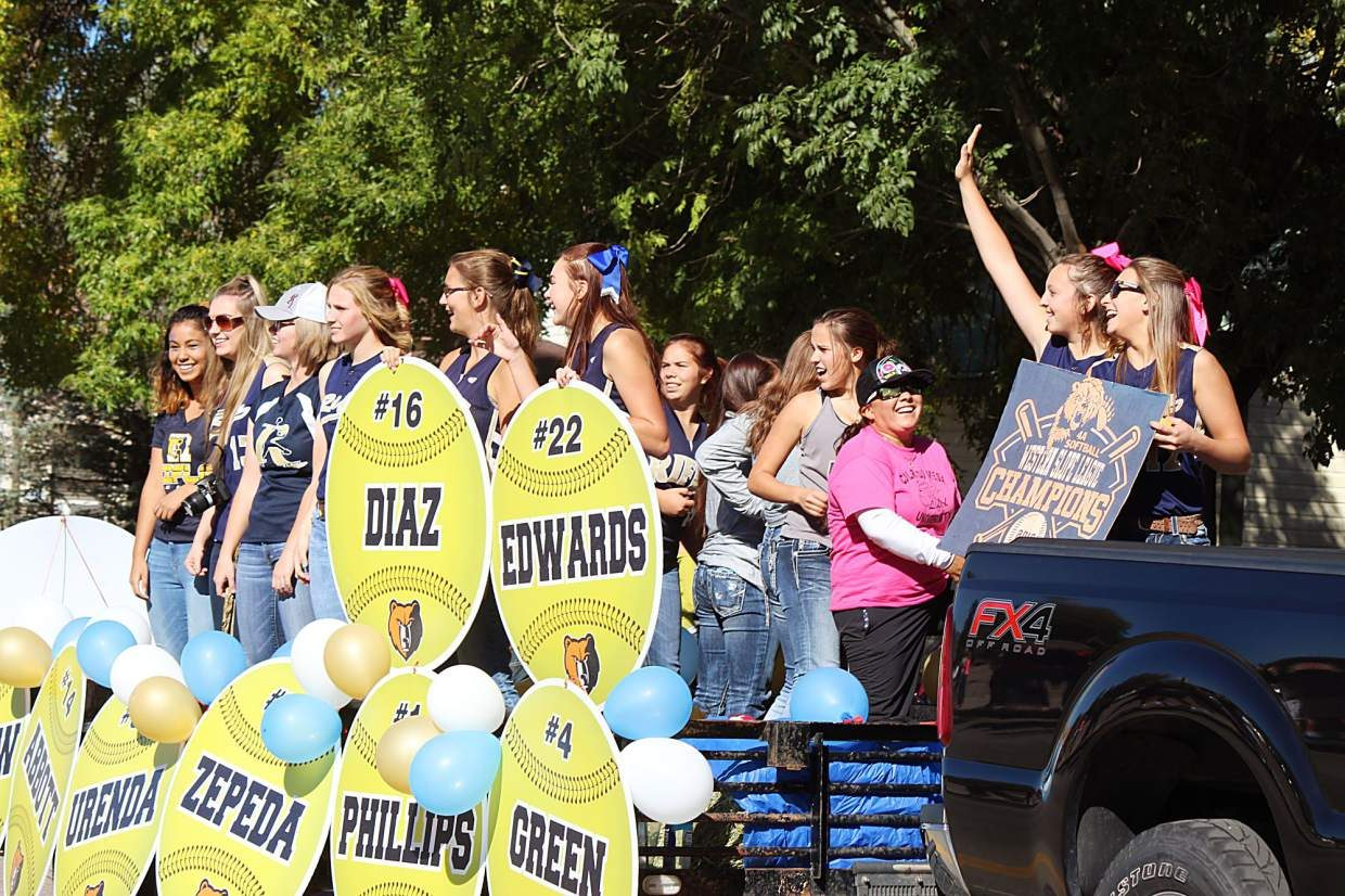 The Rifle High School softball team homecoming float makes its way down Railroad Avenue Friday.