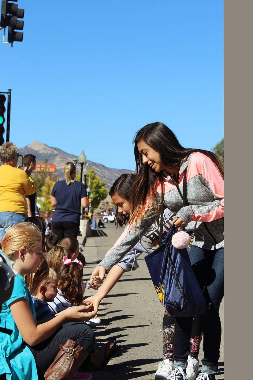 Candy is handed out during the Rifle homecoming parade Friday.