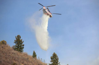 A helicopter drops water on the fire burning near Ruedi Reservoir.