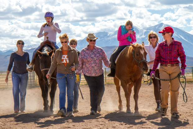 Multple volunteers work with clients Gwen Carew and Amanda VanDeursen during their sessions with the horses.