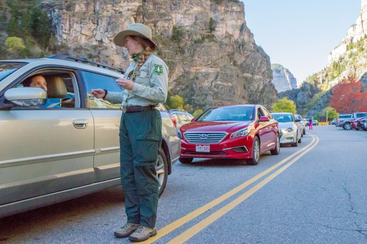 Autumn Grennier speaks with visitors who are waiting in line to get into the Hanging Lake parking lot during a busy Saturday morning. During the busy summer months there are upwards of five rangers working at Hanging Lake to control traffic and the hundreds of people who visit the lake throughout the day.