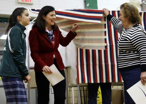 A poll worker lifts the curtain as Sen. Kelly Ayotte, R-N.H., center, leaves the voting booth with her daughter, Kate, Tuesday, Nov. 8, 2016, at Charlotte Avenue Elementary School in Nashua, N.H. (AP Photo/Elise Amendola)
