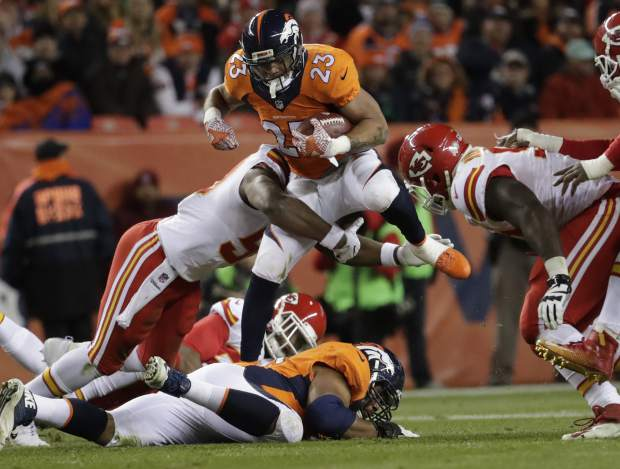Denver Broncos running back Devontae Booker (23) is hit by Kansas City Chiefs outside linebacker Justin Houston (50) during the first half of an NFL football game, Sunday, Nov. 27, 2016, in Denver. (AP Photo/Jack Dempsey)