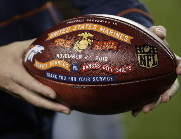 A U.S. Marine holds a football after being recognized at half time of an NFL football game between the Kansas City Chiefs and the Denver Broncos, Sunday, Nov. 27, 2016, in Denver. (AP Photo/Jack Dempsey)
