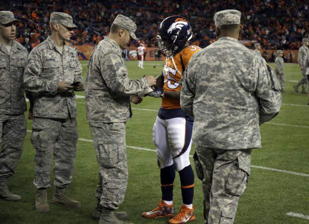 Military personal greet Denver Broncos running back Kapri Bibbs (35) at half time of an NFL football game against the Kansas City Chiefs Sunday, Nov. 27, 2016, in Denver. (AP Photo/Jack Dempsey)