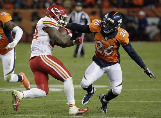 Denver Broncos free safety Darian Stewart (26) reaches for Kansas City Chiefs running back Spencer Ware (32) during the second half of an NFL football game, Sunday, Nov. 27, 2016, in Denver. (AP Photo/Jack Dempsey)