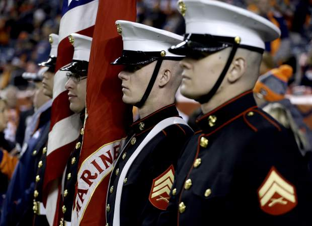 U.S. Marines stand at attention prior to an NFL football game between the Kansas City Chiefs and the Denver Broncos, Sunday, Nov. 27, 2016, in Denver. (AP Photo/Jack Dempsey)