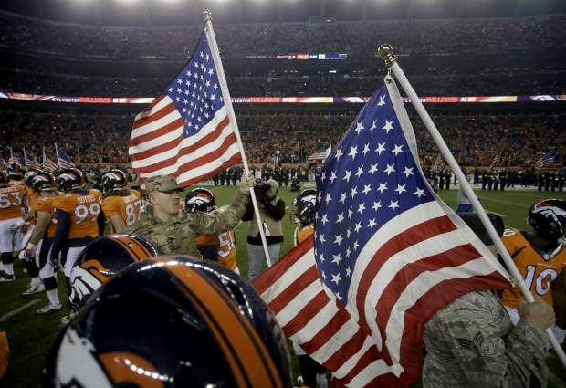Military personal carry flags as the Denver Broncos are introduced prior to an NFL football game against the Kansas City Chiefs, Sunday, Nov. 27, 2016, in Denver. (AP Photo/Joe Mahoney)