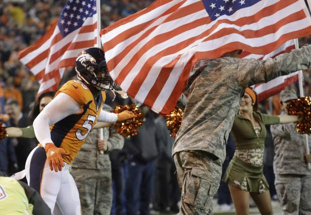 Military personal carry flags as Denver Broncos outside linebacker Von Miller (58) is introduced prior to an NFL football game against the Kansas City Chiefs, Sunday, Nov. 27, 2016, in Denver. (AP Photo/Jack Dempsey)