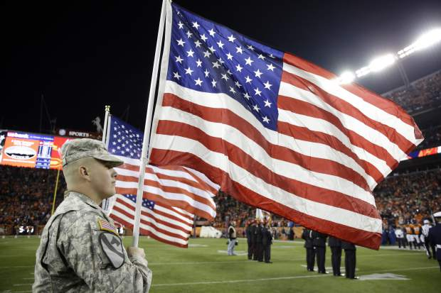 Military personal carry flags as the Denver Broncos are introduced prior to an NFL football game against the Kansas City Chiefs, Sunday, Nov. 27, 2016, in Denver. (AP Photo/Jack Dempsey)