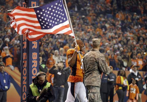 Military personal carry flags as Denver Broncos cornerback Aqib Talib (21) is introduced prior to an NFL football game against the Kansas City Chiefs, Sunday, Nov. 27, 2016, in Denver. (AP Photo/Jack Dempsey)