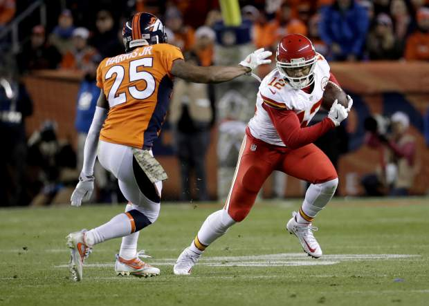 Kansas City Chiefs wide receiver Albert Wilson (12) tries to elude Denver Broncos cornerback Chris Harris (25) during the first half of an NFL football game, Sunday, Nov. 27, 2016, in Denver. (AP Photo/Jack Dempsey)