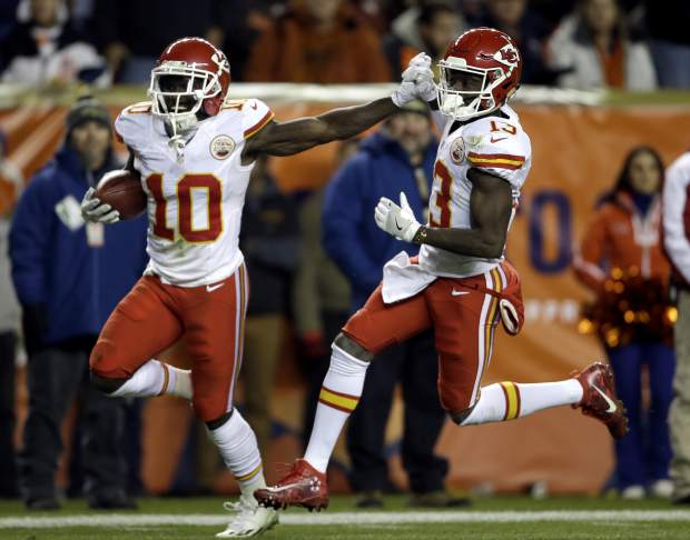 Kansas City Chiefs wide receiver Tyreek Hill (10) high fives teammate De'Anthony Thomas (13) as he runs back a punt for a touchdown against the Denver Broncos during the first half of an NFL football game, Sunday, Nov. 27, 2016, in Denver. (AP Photo/Joe Mahoney)