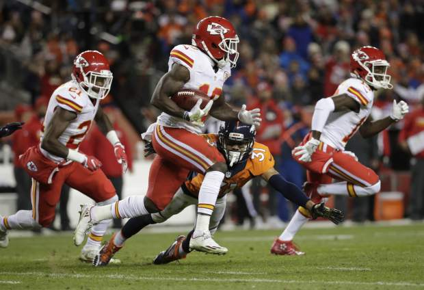 Kansas City Chiefs wide receiver Tyreek Hill (10) runs back a punt for a touchdown as Denver Broncos free safety Justin Simmons (31) defends  during the first half of an NFL football game, Sunday, Nov. 27, 2016, in Denver. (AP Photo/Jack Dempsey)