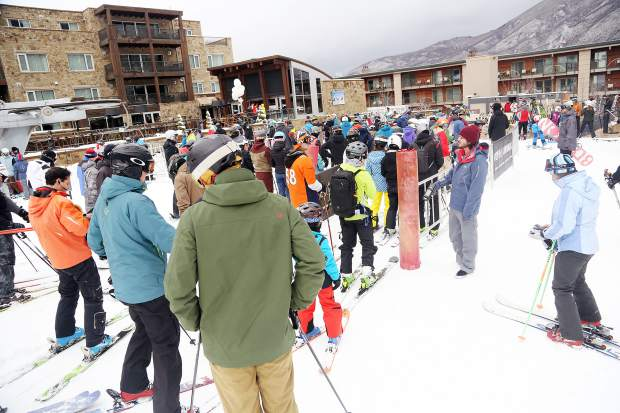 People wait in line for the Little Nell lift on Sunday, the only operational chairlift at Aspen Mountain on its opening day.