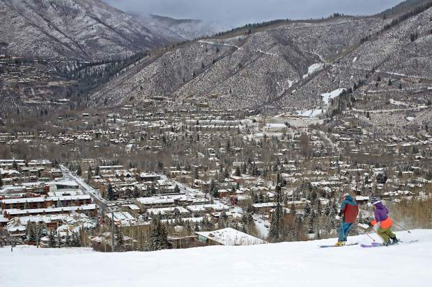 Skiers make turns on the Little Nell trail Sunday with a snowy Aspen waiting below.