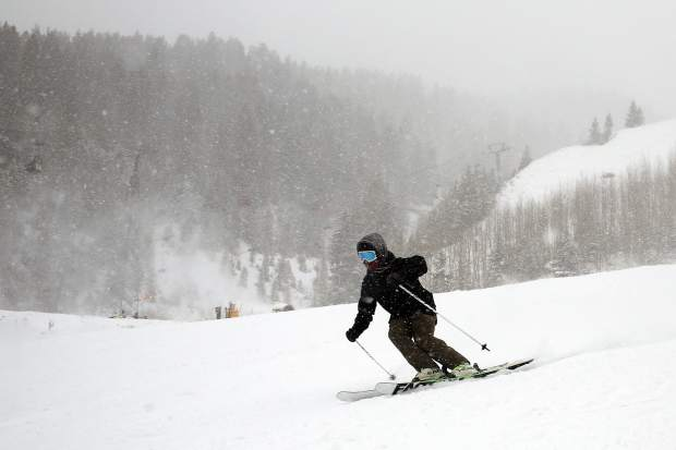 A skier makes turns through heavy snowfall Sunday on Aspen Mountain.