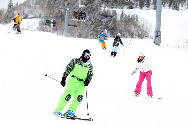 Skiers and snowboarders make turns on the Little Nell trail Sunday at the base of Aspen Mountain.