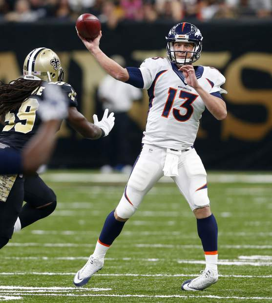 Denver Broncos quarterback Trevor Siemian (13) passes under pressure from New Orleans Saints outside linebacker Dannell Ellerbe (59) in the first half of an NFL football game in New Orleans, Sunday, Nov. 13, 2016. (AP Photo/Butch Dill)