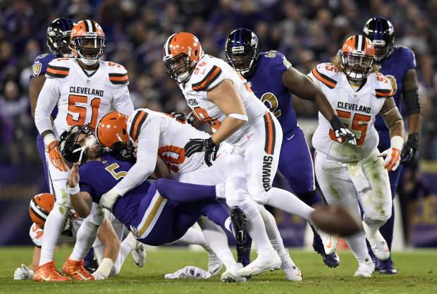 Baltimore Ravens quarterback Joe Flacco (5) is tackled by Cleveland Browns outside linebacker Emmanuel Ogbah in the first half an NFL football game, Thursday, Nov. 10, 2016, in Baltimore. (AP Photo/Gail Burton)