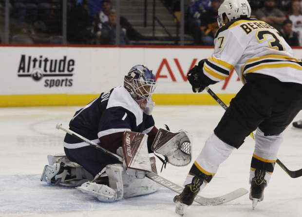 Colorado Avalanche goalie Semyon Varlamov, left, of Russia, makes a stick save of a shot by Boston Bruins center Patrice Bergeron in the second period of an NHL hockey game, Sunday, Nov. 13, 2016, in Denver. (AP Photo/David Zalubowski)