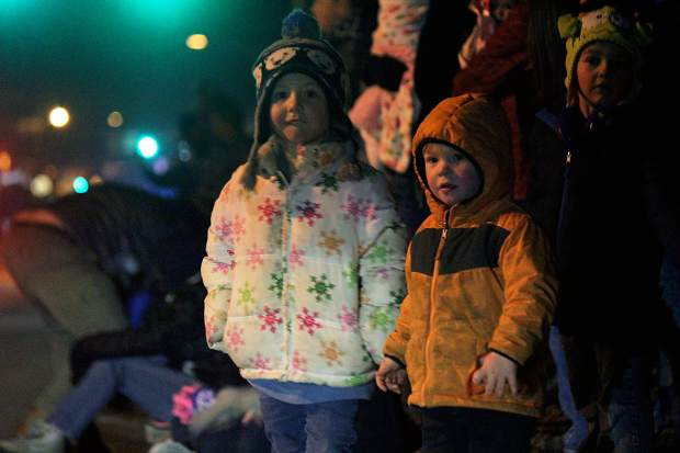 Abigail, left, and Kylee Anthony watch as the 2015 Hometown Holiday Celebration Parade of Lights rolls down Railroad Avenue.