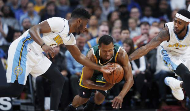 Utah Jazz guard Rodney Hood, center, tries to pick up a loose ball as Denver Nuggets guards Emmanuel Mudiay, left, and Will Barton defend in the first half of an NBA basketball game Sunday, Nov. 20, 2016, in Denver. (AP Photo/David Zalubowski)