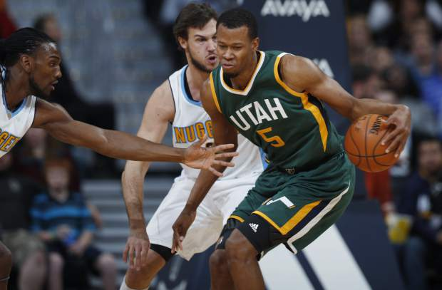 Utah Jazz guard Rodney Hood, front right, works the ball inside as Denver Nuggets forwards Danilo Gallinari, of Italy, back right, and Kenneth Faried defend in the first half of an NBA basketball game Sunday, Nov. 20, 2016, in Denver. (AP Photo/David Zalubowski)