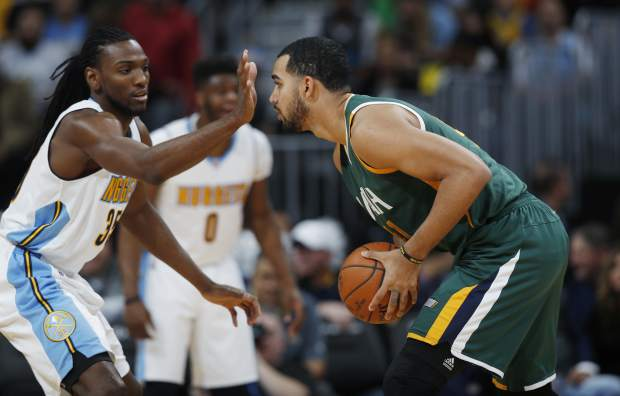 Denver Nuggets forward Kenneth Faried obstructs the view of Utah Jazz forward Trey Lyles as he looks to pass the ball in the first half of an NBA basketball game Sunday, Nov. 20, 2016, in Denver. (AP Photo/David Zalubowski)