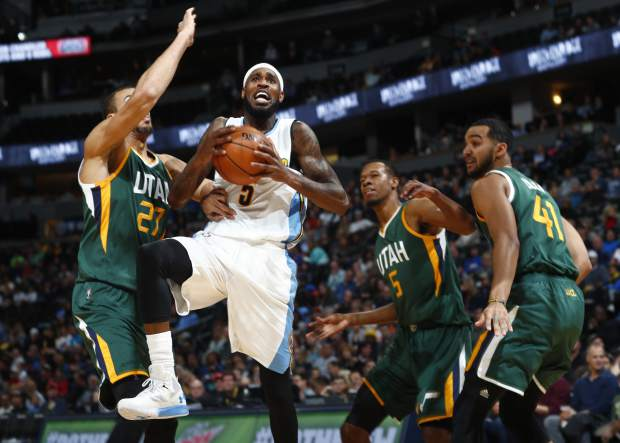 Denver Nuggets guard Will Barton, second from left, drives the lane to the basket as, from left, Utah Jazz center Rudy Gobert, of France, guard Rodney Hood and forward Trey Lyles defend in the first half of an NBA basketball game Sunday, Nov. 20, 2016, in Denver. (AP Photo/David Zalubowski)