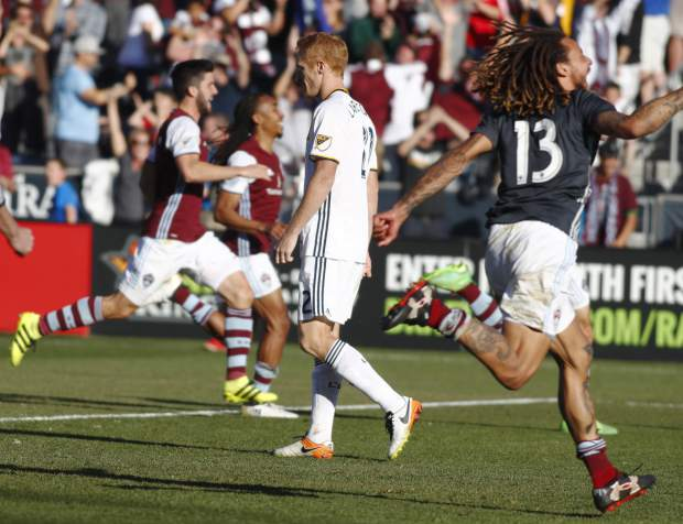 As players run on to the pitch to celebrate, Los Angeles Galaxy defender Jeff Larentowicz, center, walks away after having his kick stopped by Colorado Rapids goalkeeper Tim Howard in the second leg soccer match of the Western Conference semifinals of the MLS cup playoffs in Commerce City, Colo., on Sunday, Nov. 6, 2016. Colorado won 1-0 and advances to the next round of the playoffs. (AP Photo/David Zalubowski)