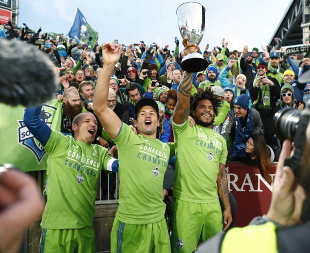 From left to right, Seattle Sounders midfielder Osvaldo Alonso, forward Nelson Haedo Valdez and defender Roman Torres celebrate with fans after defeating Colorado in the second leg of the MLS Western Conference soccer finals Sunday, Nov. 27, 2016, in Commerce City, Colo. (AP Photo/David Zalubowski)