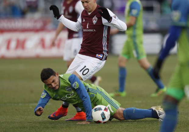 Seattle Sounders midfielder Cristian Roldan, front, falls while pursuing the ball with Colorado Rapids midfielder Marco Pappa in the second half of the second leg of an MLS Western Conference soccer finals game Sunday, Nov. 27, 2016, in Commerce City, Colo. Seattle won 1-0 to advance to the MLS championship game. (AP Photo/David Zalubowski)