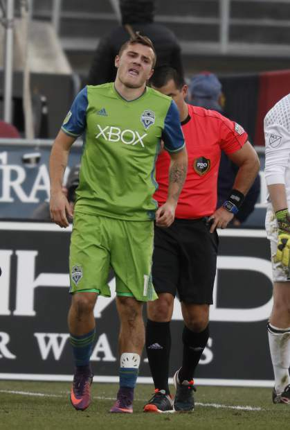 Seattle Sounders forward Jordan Morris hobbles to the bench for medical help after being slightly injured while scoring a goal against the Colorado Rapids in the second half of the second leg of an MLS Western Conference soccer finals game Sunday, Nov. 27, 2016, in Commerce City, Colo. Seattle won 1-0 to advance to the MLS championship game. Morris remained in the game. (AP Photo/David Zalubowski)