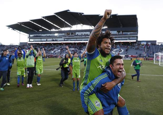 Seattle Sounders defender Roman Torres, top, is given a ride by forward Herculez Gomez as they celebrate with teammates after defeating the Colorado Rapids in the second leg of the MLS Western Conference soccer finals Sunday, Nov. 27, 2016, in Commerce City, Colo. (AP Photo/David Zalubowski)