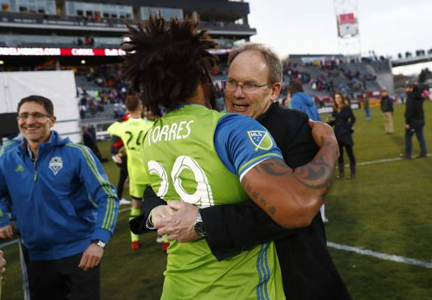 Seattle Sounders defender Roman Torres, front, hugs head coach Brian Schmetzer after defeating the Colorado Rapids in the second leg of the MLS Western Conference soccer finals Sunday, Nov. 27, 2016, in Commerce City, Colo. (AP Photo/David Zalubowski)