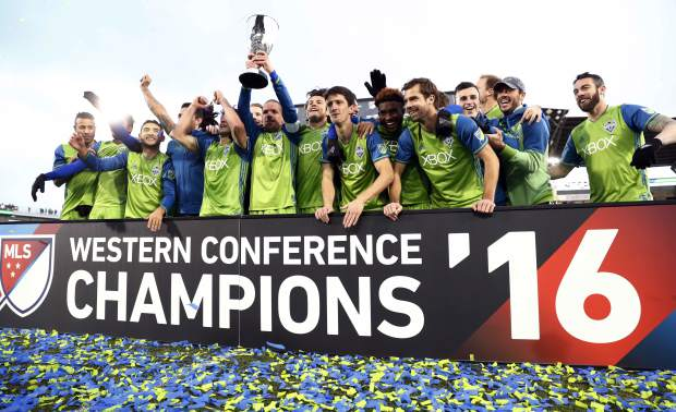 Seattle Sounders players celebrate with the trophy after defeating Colorado in the second leg of the MLS Western Conference soccer finals Sunday, Nov. 27, 2016, in Commerce City, Colo. (AP Photo/David Zalubowski)