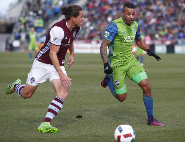 Colorado Rapids defender Marc Burch, left, pursues the ball with Seattle Sounders defender Tyrone Mears in the first half of the second leg of an MLS Western Conference soccer finals Sunday, Nov. 27, 2016, in Commerce City, Colo. (AP Photo/David Zalubowski)