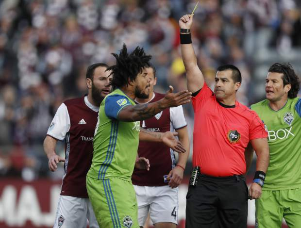 Seattle Sounders defender Roman Torres, left, argues after he was issued a yellow card while facing the Colorado Rapids in the first half of the second leg of an MLS Western Conference soccer finals Sunday, Nov. 27, 2016, in Commerce City, Colo. (AP Photo/David Zalubowski)