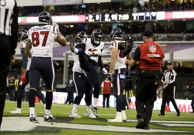 Houston Texans wide receiver Braxton Miller celebrates with teammate guard Xavier Su'a-Filo, below, after scoring a touchdown during the first half of an NFL football game against the Oakland Raiders Monday, Nov. 21, 2016, in Mexico City. (AP Photo/Rebecca Blackwell)