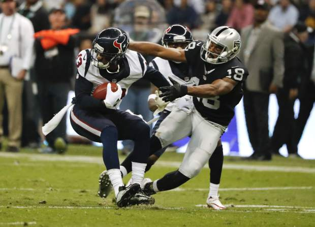 Houston Texans wide receiver Braxton Miller gets away from the Oakland Raider Andre Holmes (18) during the first half of an NFL football game Monday, Nov. 21, 2016, in Mexico City. (AP Photo/Eduardo Verdugo)