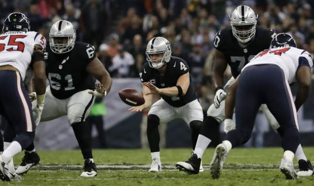 Oakland Raiders quarterback Derek Carr takes a snap during the first half of an NFL football game against the Houston Texans Monday, Nov. 21, 2016, in Mexico City. (AP Photo/Rebecca Blackwell)