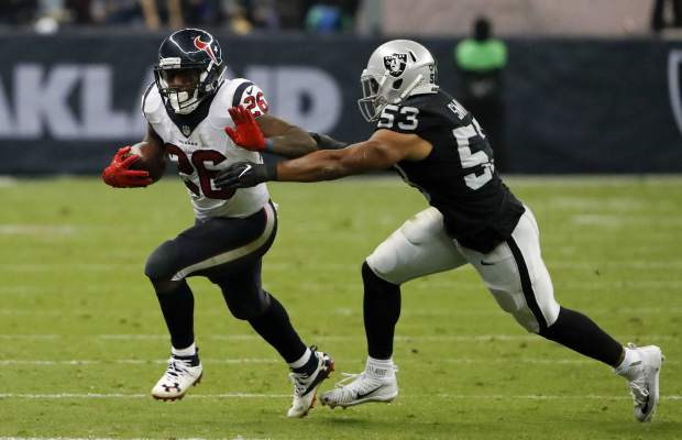 Houston Texans running back Lamar Miller (26) runs past Oakland Raiders outside linebacker Malcolm Smith during the second half of an NFL football game Monday, Nov. 21, 2016, in Mexico City. (AP Photo/Eduardo Verdugo)