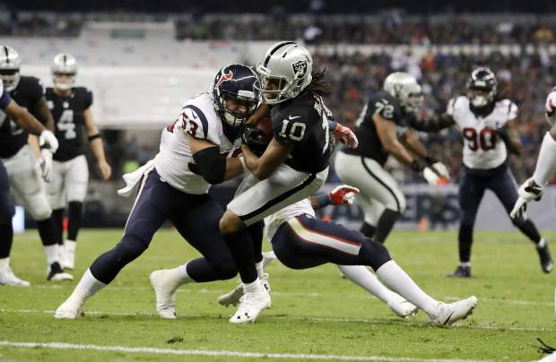 Oakland Raiders wide receiver Seth Roberts is brought down by Houston Texans inside linebacker Max Bullough during the second half of an NFL football game Monday, Nov. 21, 2016, in Mexico City. (AP Photo/Rebecca Blackwell)