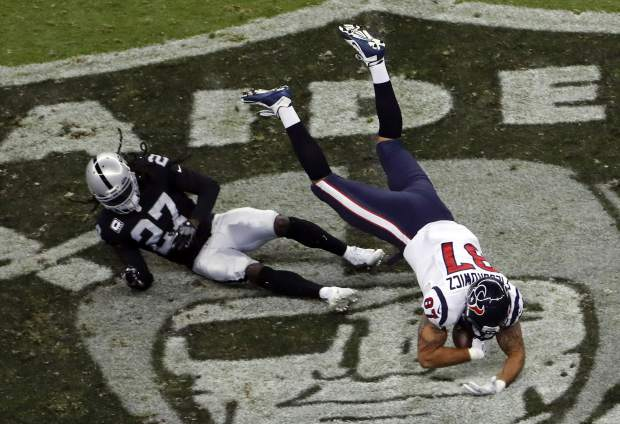 Houston Texans tight end C.J. Fiedorowicz makes a catch over Oakland Raiders free safety Reggie Nelson (27) during the first half of an NFL football game Monday, Nov. 21, 2016, in Mexico City. (AP Photo/Dario Lopez-Mills)