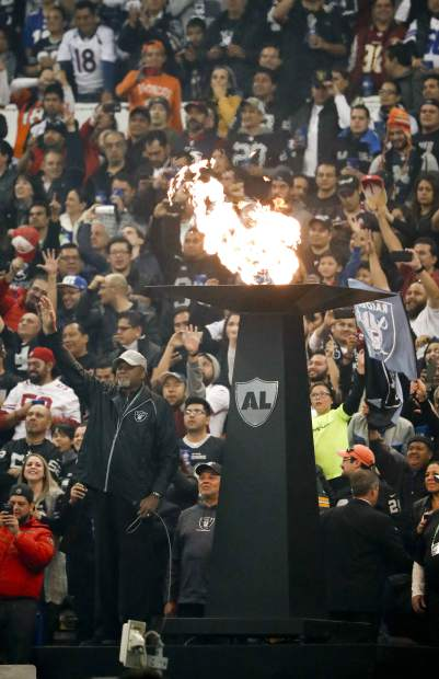 Tommie Smith, below left, lights the torch in in honor of former Oakland Raiders before an NFL football game Monday, Nov. 21, 2016, in Mexico City. Smith is famous for his 1968 Olympics protest. (AP Photo/Eduardo Verdugo)