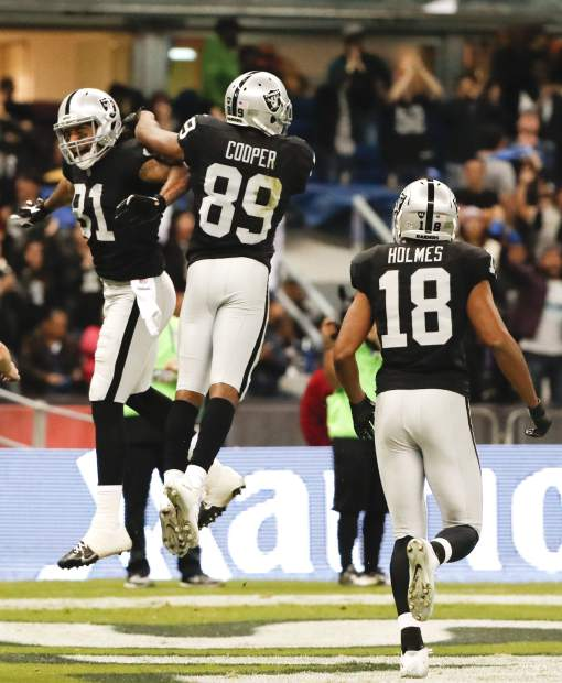 Oakland Raiders wide receiver Amari Cooper, center, celebrates his touchdown with teammates during the second half of an NFL football game against the Houston Texans Monday, Nov. 21, 2016, in Mexico City. (AP Photo/Eduardo Verdugo)